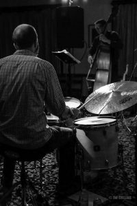 Black and white photo of a drummer playing a drumset