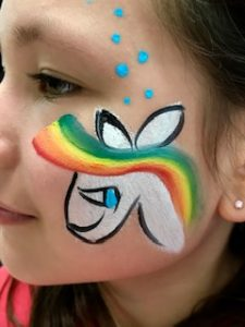 rainbow unicorn facepainting on a young girl's face