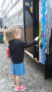 Little girl painting at the Art Bus